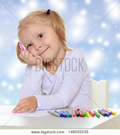 Pretty little blonde girl drawing with markers at the table.Girl put head on his hand , she dreams about something.The concept of celebrating the New year, Holy Christmas