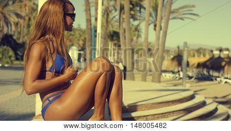 Happy African Girl in Bikini Sits at Beach Bench