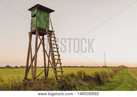 Wooden Hunting high tower on the meadow. Hunters lookout tower.