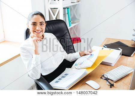 Smiling happy businesswoman holding reports and looking at camera while sitting at the workplace