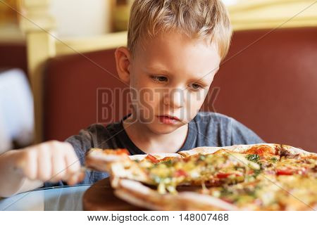 Adorable Little Boy Eating Pizza At A Restaurant