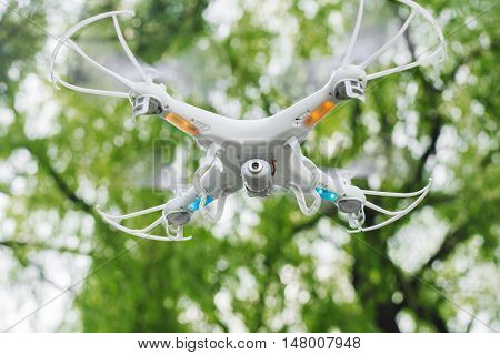 Drone with camera while flying in the forest. Unmanned aerial copter flight. Modern tool for making photo and video, searching, watching. Aeromodelling, hobby, modern technologies