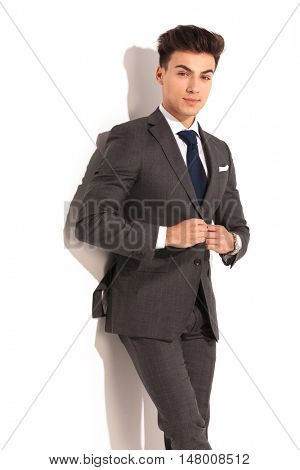 attractive young man in suit and tie unbuttoning his coat on white background