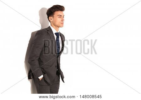 side view of a relaxed young business man with hands in pockets on white background
