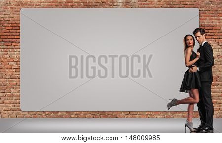 elegant young couple standing embraced near big billboard on a brick wall