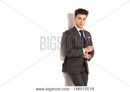handsome young business man fixing his sleeve and looks at the camera in studio
