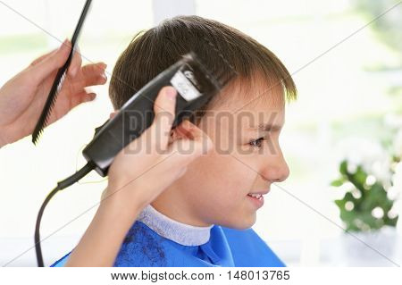 Portrait of boy getting haircut from female hairdresser at salon