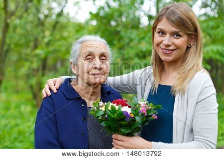 Portrait of a happy senior woman receiving flowers from her granddaughter