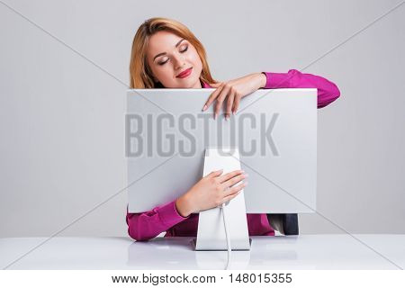 young woman sitting in the table and using computer on gray background. satisfied smiling girl hugging Monitor