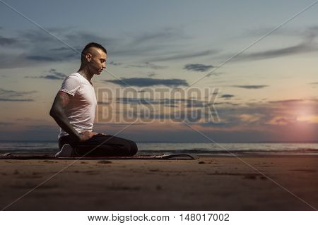 Young caucasian man with tattoos sitting and meditating on the beach at sunset. Yoga Meditation Pose.