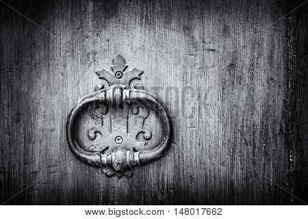 old handle with knocker of a wooden door black and white