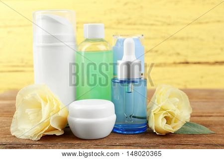 Different cosmetic bottles and eustoma flowers on yellow wall background