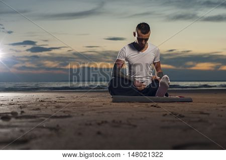 Serene young flexible man with tattoos on the body sitting on the beach and doing stretching exercises before yoga practice.
