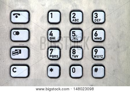 Public phone metal console with different buttons.