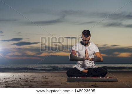 Young man with tattoos sitting on the beach on lotus position and meditating outdoors. High level yoga practice.