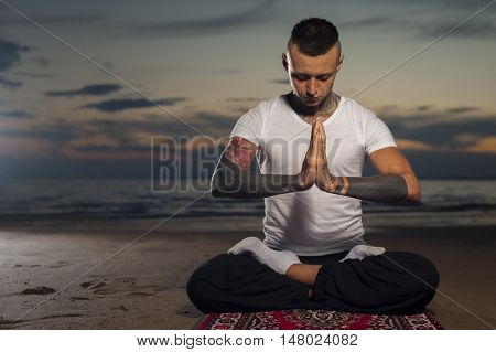 Young attractive man with tattoos on body sitting on the beach at sunset and meditating. Advanced yoga practice, lotus pose.