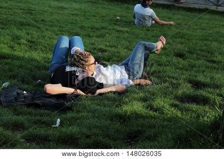 PARIS, FRANCE - MAY 12, 2015: Unknown young couple are relaxing in the sunset sun on the slopes of Montmartre near the Sacre Coeur.