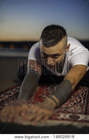 Portrait of young flexible man with tattoos practicing yoga on the beach at sunset
