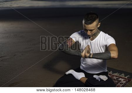 Young attractive man with tattoos sitting on the beach in lotus position and meditating. Yoga practice outdoors.