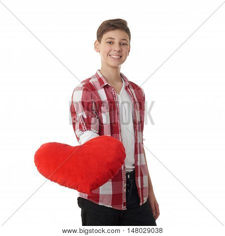 Cute teenager boy in red checkered shirt with plush heart over white isolated background, half body