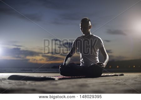 Yoga practice outdoors: young man sitting on the beach and meditating.