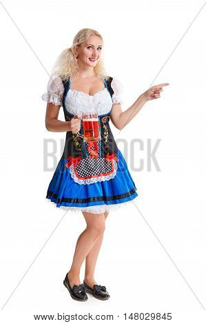 Beautiful young blond girl in dirndl drinks out of oktoberfest beer stein. Isolated on white background. she holds a glass with a drink and smiling. full height. pointing finger and smiling. copyspace