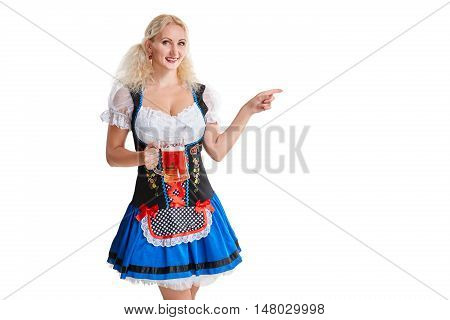Beautiful young blond girl in dirndl drinks out of oktoberfest beer stein. Isolated white background. she holds a glass with a drink and smiling. pointing finger and smiling. copyspace desing concept