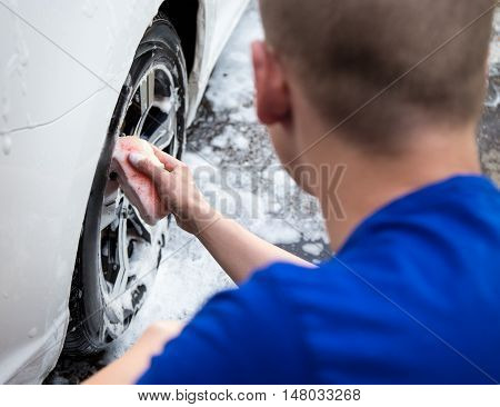 Handle Carwash Concept - Back View Of Man Washing Car Wheel With Sponge