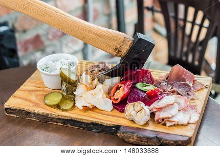 Slices fresh pork meat, lard on wooden board with vegetables, spices, stuck ax on the table
