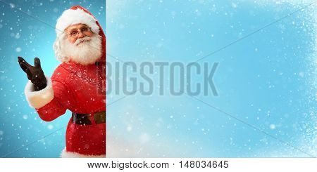Jolly Santa Claus holding banner with blue space for Your Text. Merry Christmas & New Year's Eve concept. Close up on blurred blue background.