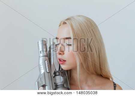 Close up portrait of a beautiful fashion blonde girl in silver shiny dress holding water gun isolated on the grey background