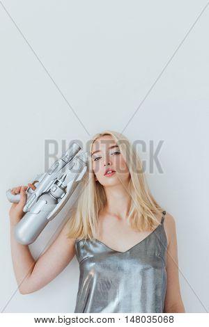 Close up portrait of a beautiful fashion blonde girl in silver shiny dress pointing gun at herself isolated on the grey background