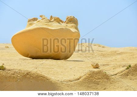 The large, smooth stone out of the sand lies on a sandy surface on blue sky background
