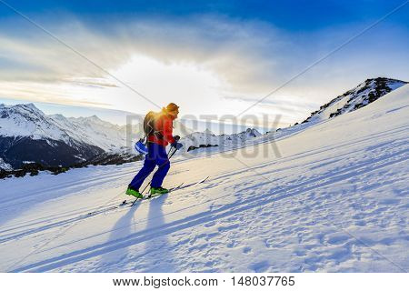 Ski touring man reaching the top at sunrise in Swiss Alps.
