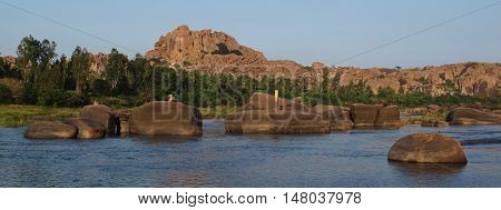 Unique landscape in Hampi India. Tungabhadra River and granite mountain. Popular travel destination and UNESCO world heritage site.