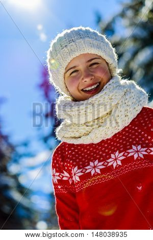 Happy winter girl wearing knitted wear scarf. Excited beautiful smiling teenager posing in winter background.