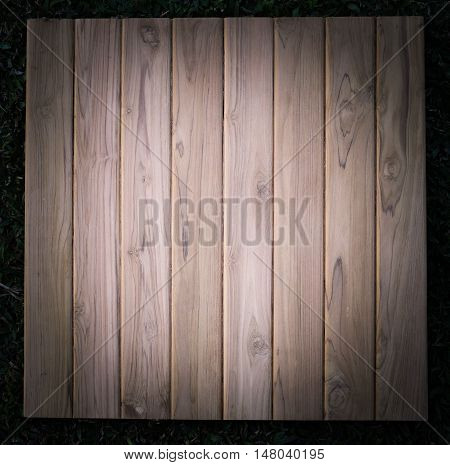 Teak wood board on grass use for background.