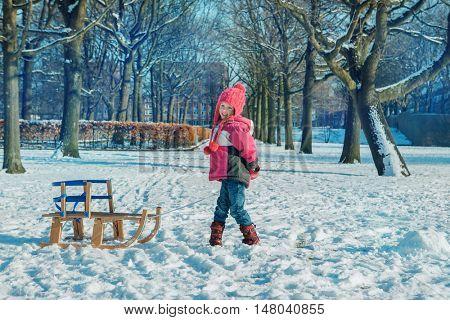 Preschooler with sleigh in a snowy park