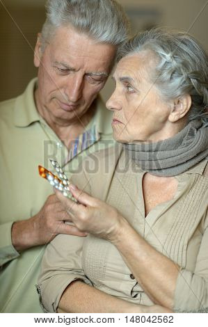 Portrait of ill senior couple with a pills