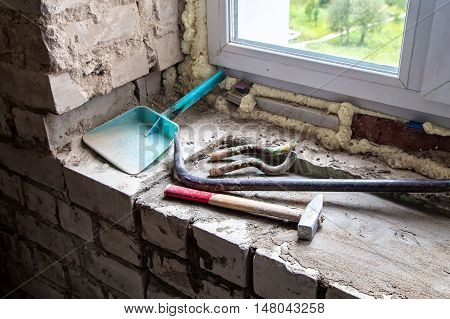 Dirty building tools on the window-sill during overhaul