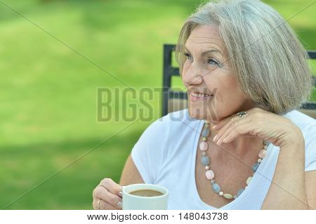 Elder woman with breakfast and coffee outside