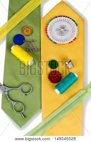 Sewing tools on top of neck ties- scissors, buttons, sewing pins, safety pins, zippers, thread and fabric
