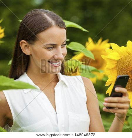 Happy young woman calling by phone. Close up portrait of beautiful joyful brunette with sunflower