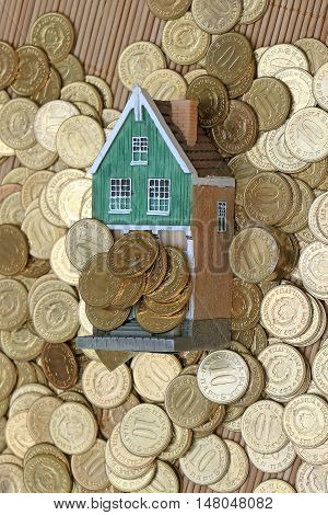 Large pile of gold coins beneath and over model house