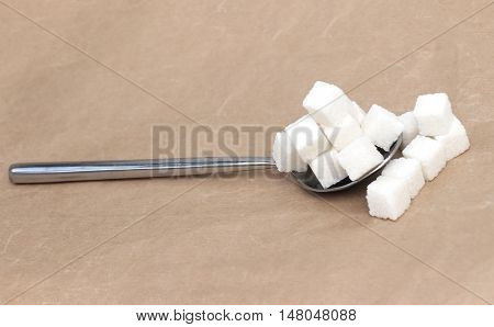 Big pile of white sugar cubes on silver spoon overflowing on the side