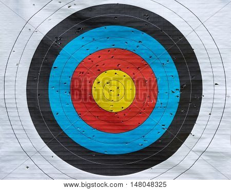 Colored paper target with many hits from archery in close-up