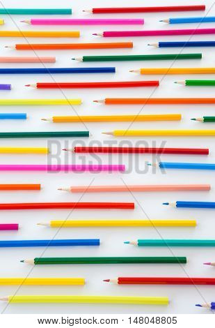 Colorful crayons in parallel lines on white