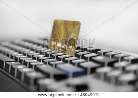 Golden card on a background of gray computer keyboard in a dark key