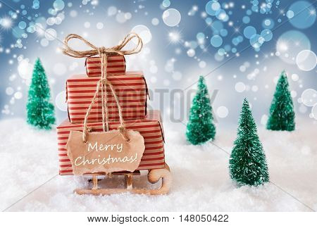 Sleigh Or Sled With Christmas Gifts Or Presents. Snowy Scenery With Snow And Trees. Blue Sparkling Background With Bokeh Effect. Label With English Text Merry Christmas
