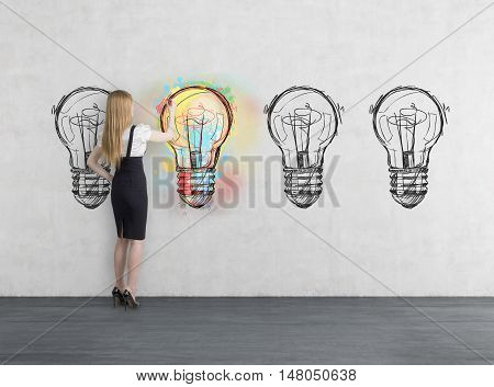 Side view of businesswoman coloring one of four light bulb sketches on concrete wall. Concept of choice and making progress. Toned image